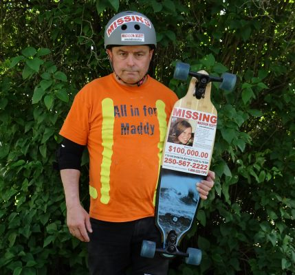 All in for Maddy. Maddy's uncle holding skateboard and wearing helmet, both with Madison Scott Missing stickers.